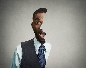 Shocked, surprised business man on grey wall background