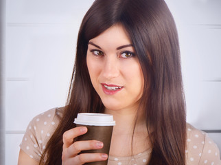 Woman with Coffee in To-Go Cup indoors.