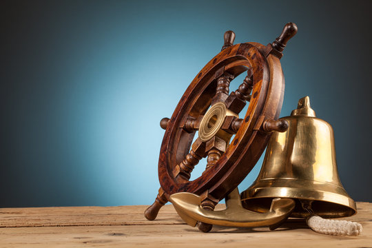 maritime adventure  anchor bell and old wooden steering wheel