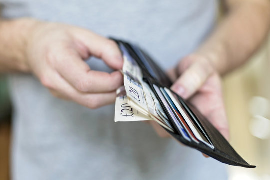 Man with cash inside wallet