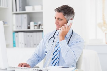 Doctor using telephone while working on computer