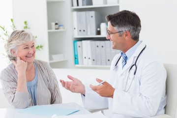 Doctor discussing with senior patient at table
