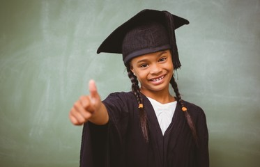 Girl in graduation robe gesturing thumbs up