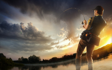 Poster Peche Young man fishing at dramatic sunset
