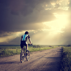 Epic Photo of Cyclist on Dramatic Sky Background