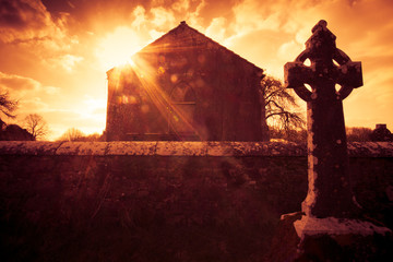 Ireland celtic cross at medieval cemetery under fiery sky