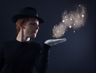 Fototapeta young magician in a black hat and white gloves