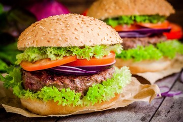homemade hamburgers with green lettuce, tomatoes and red onions