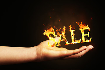 Hand with word Sale made of fire flame isolated on black