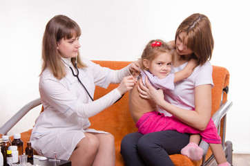 Doctor listening stethoscope back at girl sitting of mother