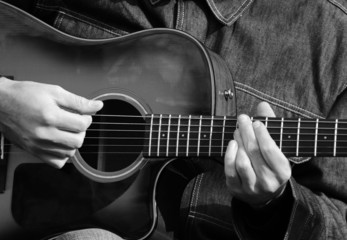 Close up of male hands playing guitar in black and white