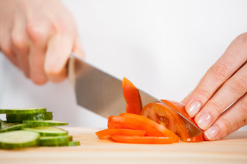 Female hands cutting fresh cucumber and tomato