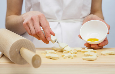 Cook spreading uncooked pastry with yolk