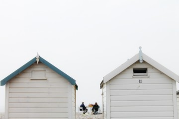 A couple having a picnic next to beach huts on an overcast day