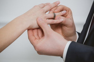 Groom put a ring on finger of his lovely wife.
