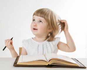 Smiling little girl holding a pen and looking up