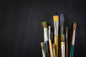 paint brushes in jar over blackboard background