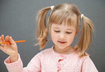 Beautiful little girl holding an orange   pencil