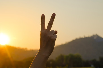 Hand showing peace victory sign against pure blue sky