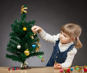 Beautiful little girl decorates the Christmas tree