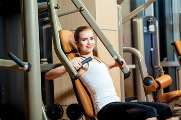 young woman flexing muscles on gym machine