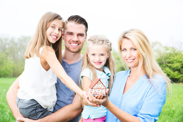 Familie mit Haus in der Hand