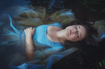 Young beautiful drowned woman in blue dress lying in the river