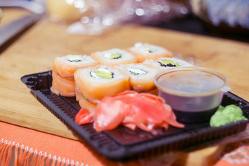 Open pack of sushi with soy sauce and ginger