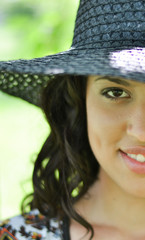Half face shot of brunette girl with straw hat