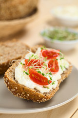 Bread with cream cheese, cherry tomato and alfalfa sprouts