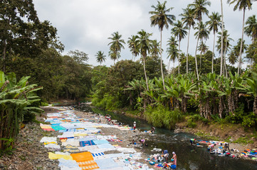 African women washing clothes on a river in the jungle