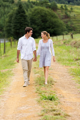 couple holding hands walking in countryside