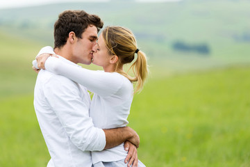 romantic couple kissing on grassland