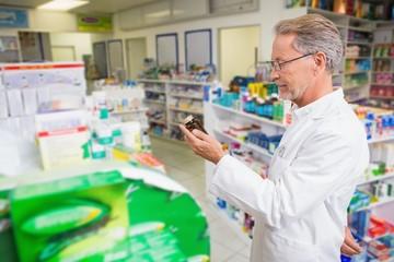 Senior pharmacist looking at medicine