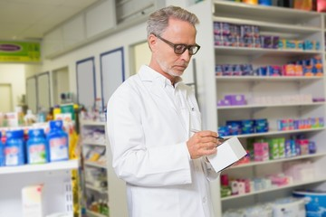 Focused pharmacist writing on box of medicine