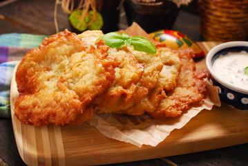 potato cakes lying on wooden board with bowl of  vegetable and m
