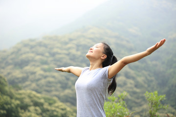 cheering young woman open arms on mountain peak