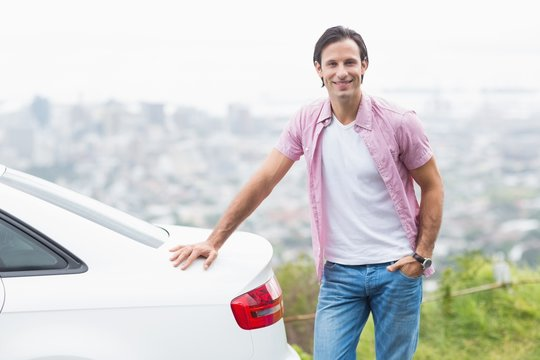 Smiling man standing next to his car