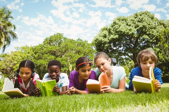 Children lying on grass and reading books