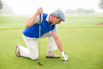 Happy golfer kneeling on the putting green