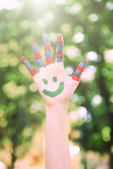 Smiling colorful hand on sunny natural background