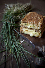 double sandwich with omelette and chives on rustic wooden table