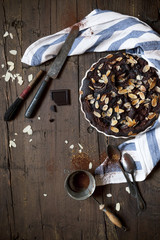 dark chocolate and almonds cake on wooden table