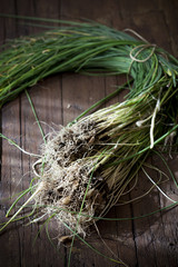 bunch of wild chives with roots on wooden table