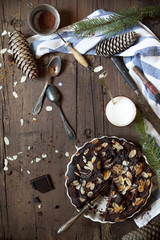 dark chocolate and almonds cake on table with pine branches