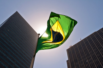 Photo sur Aluminium Amérique du Sud Brazilian National Flag against Skyscrapers by Sunset