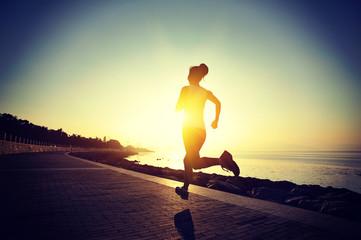 woman runner athlete running at sunrise seaside
