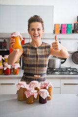 Happy young housewife showing jars with homemade fruits jam