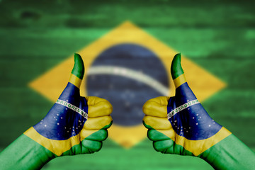 Brazil flag painted on female hands thumbs up