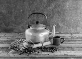 Old kettle,paper roll,rope reel and coffee beans on wooden backg